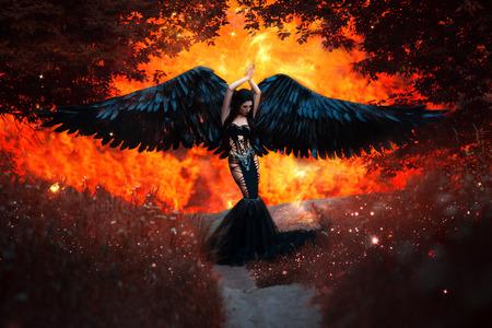 Schwarzer Engel. Hübsches Mädchen-Dämon mit schwarzen Flügeln. Ein Bild für Halloween. Bild eines alten Märchenbuch. Modische Tonung Standard-Bild
