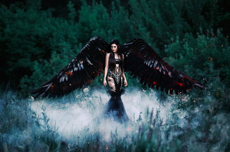 Black Angel. Pretty girl-demon with black wings. An image for Halloween. Image of an old book of fairy tales. Fashionable toning
