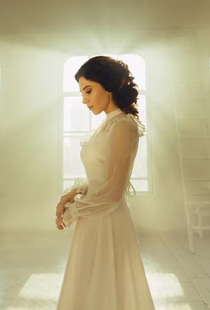 Lady in vintage white dress debout dans une grande chambre spacieuse, tir fantastique, princesse de conte de fées transformé en fumée, tonifiant à la mode, les couleurs informatiques créatives Banque d'images