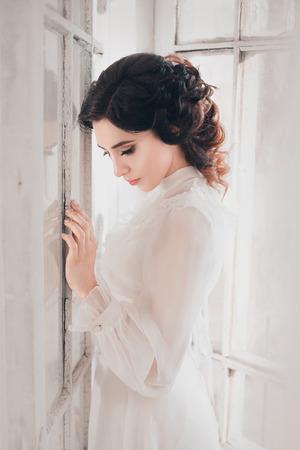 Dame im weißen Vintage-Kleid stehen in einem großen geräumigen Zimmer, fantastische Schuss, Märchenprinzessin verwandelte sich in Rauch, trendy Tonen, kreativ Computer Farben Standard-Bild