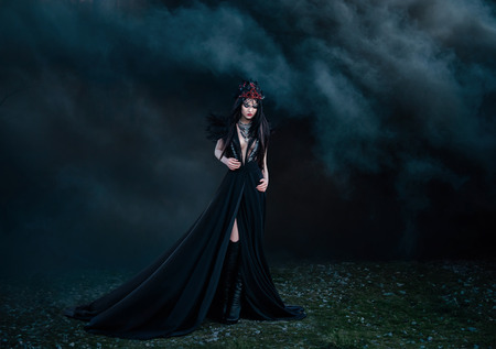 fine legs: dark evil queen way through the smoke screen of the movie cosplay snow white and the Huntsman wild Princess, vampire, hip toning, creative color, dark boho Stock Photo