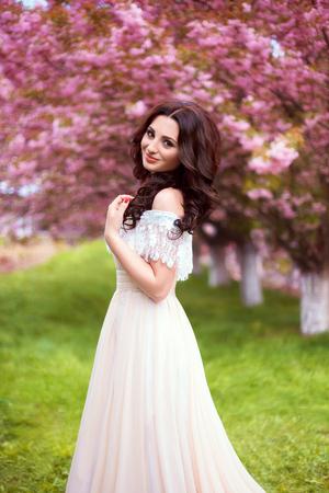 bella passeggiata di primavera nei boschi tra i fiori di ciliegio in Aprila signora in un lungo abito color pastello, i colori del computer creativi, tonificante alla moda