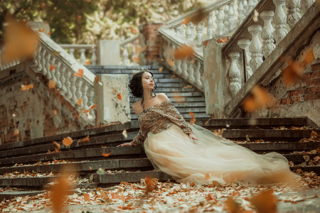 Beautiful girl in a luxurious dress walks in autumn park near the castle.Princess sits on the steps of the fall of the castle.Fashionable toning.creative colors Imagens