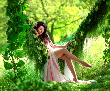 beautiful girl in pale pink with platne chern?mi curls sitting in the grass in the middle of the jungle hammock, Tropikanka with flower, hip toning, creative color 版權商用圖片