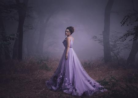 緑豊かな紫色のドレス渦巻く煙、幻想的なショットで高級で女性、おとぎ話の王女は秋の森では、ファッショナブルな創造的なコンピューターの色