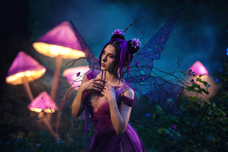 Fantastic photo shoot.  Fairy Coquette standing near the huge mushroom. Background fairy forest, scenery shine. The unusual fairy-tale image, purple dress and torn wings. Fashionable toning. Stock Photo