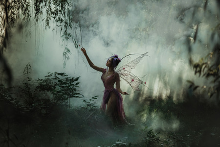 Fantastic photo shoot with smoke. Fairy Coquette walking in the fog. Background fairy forest, vines and trees. Unusual fabulous looks, purple dress and torn wings. Fancy toning.