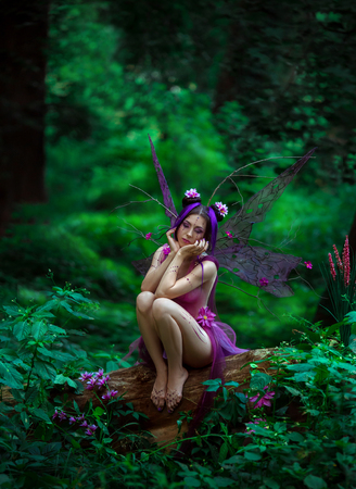 Fantastic photo shoot with smoke. Fairy Coquette sad tree. Background fairy forest, vines and trees. Unusual fabulous views, purple dress and torn wings. Fashionable toning.
