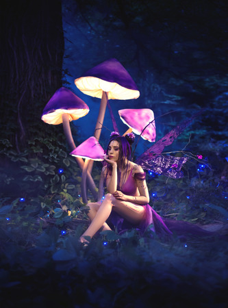 Fantastic photo shoot. Fairy sitting under huge mushrooms. Background fairy forest, scenery shine. The unusual fairy-tale image, purple dress and torn wings. Fashionable toning. Stockfoto