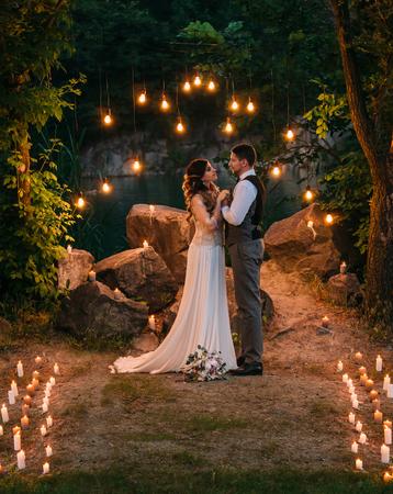 아름 다운 젊은 신부와 신랑, 사랑스럽게 서로를 찾고. 호수의 그림 같은 해안의 사진. 야생에서 결혼식입니다. 비정상적인 장식, 양 초, 전구입니다. 세련 된 토닝입니다. 스톡 콘텐츠 - 61459017