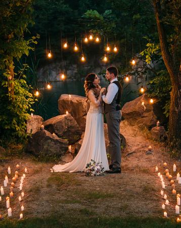 Beautiful young bride and groom,lovingly looking at each other. Photos on the picturesque shore of the lake. Wedding ceremony in the wild. Unusual decorations, candles, light bulbs.Fashionable toning.