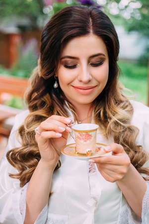 princely: lady with a Cup from an old set in the white outfit.Charming bride.Portrait outdoors in the garden. Stylish makeup .Fashionable toning