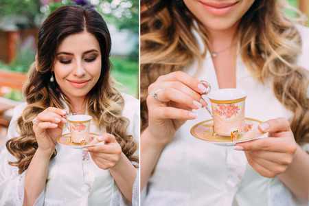 princely: Girl with charming smile dreams of holding in the hands a Cup.Beautiful bride.Stylish makeup.Luxurious hairstyle for long hair.Manicure.Engagement ring.Outdoors.Fashionable toning.