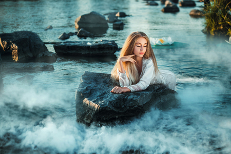 Fairy lies on a stone in water.Lake shrouded in mist. Fantastic picture. Fashionable toning