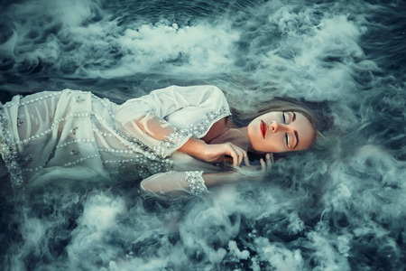 shrouded: Fairy lying in the water, shrouded in mist. Fashionable toning