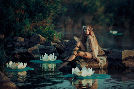 Fairy sitting on a rock in the water.Fantastic lake with big lilies. Background mysterious forest. A wreath made of shells, handmade. Fashionable toning Stock Photo