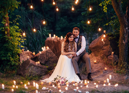 Extraordinary photo .Beautiful wedding under the open night sky.Luxurious decoration with lights and candles.Retro style.The groom gently embraces the bride.Fashionable toning.