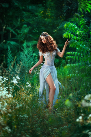 Fantastic photoshoot luxurious fairy.A long, airy, light dress and handmade jewellery.Cute beautiful Princess with long dark hair.The picturesque scenery of the magical forest world.Fashionable toning.Creative color. Stock Photo