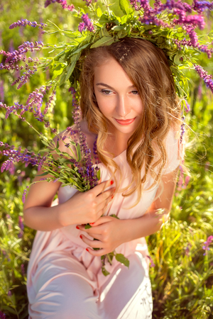 Young interesting girl in elegant dress pastel tones. A handmade wreath made of natural elements. Stylish makeup. On the background of beautiful nature. Fashion toning. Creative color.