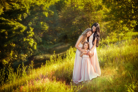 Beautiful family, a sumptuous mother and two daughters. Genuine feelings. Lady in peach-vintage dresses with pretty long hair. Photo by beautiful trees under the open sky. Fashionable toning.Creative color. Stock Photo