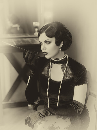 Beautiful Flapper woman with a mouthpiece. Old photo in a retro style. Smokey eyes, hairstyle cold wave.