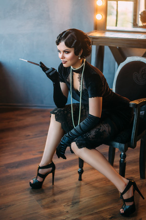 Belle femme de Flapper avec une embouchure. Vieille photo dans un style rétro. yeux Smokey, vague de froid coiffure. Banque d'images