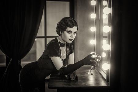 Belle fille de Flapper avec wineglass. Vieille photo dans un style rétro. yeux Smokey, vague de froid coiffure. Banque d'images - 64591689