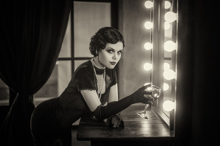 Beautiful Flapper girl with wineglass. Old photo in a retro style. Smokey eyes, hairstyle cold wave. Foto de archivo