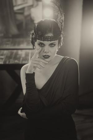 Schöne Flapper Mädchen in die Kamera schaut. Altes Foto im Retro-Stil. Rauchige Augen und Haare Kältewelle.