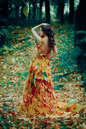 Fantastic girl in the autumn forest. Sad Queen of Nature in a luxurious dress with a leaf. Long hair. Creative colors Stockfoto