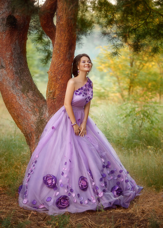 exclusive photo: Beautiful young brunette in luxury, purple, long dress with beautiful patterns. Outfit - exclusive handmade. Photo Fairy. Charming laughing a stunning Queen. Fashionable toning. Creative computer colors.