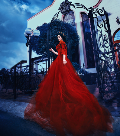 Beautiful brunette girl with long hair. Shes in a vintage red dress with bare shoulders. The Queen walks near her castle. Background extraordinary castle. Gothic history. Fashionable toning.Creative computer colors. Stock Photo