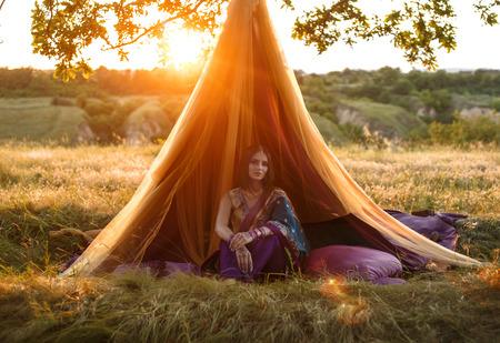 robo: Hermosa mujer con apariencia oriental pelo oscuro en traje nacional se sienta en una cabaña de cuento de hadas único. La imagen en el telón de fondo de la hermosa vida silvestre en los rayos del oro del color sunset.Fashionable tinted.Creative.