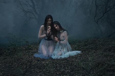 두 여자는 울다. 희생자를 기다리고 불길한 숲 숲 glade에 앉아 빈티지 드레스에 젊은 숙 녀. 공포의 스타일의 Photoshoot. 신비로운 사진. 패션 토닝. 창조