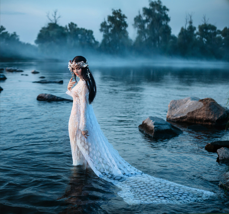 fash: Beautiful fairy in a beautiful white dress, standing in the water looking at the sinking plume among the large stones in the water.A wreath made of shells, handmade.Among the beautiful, misty forest, a mysterious, alluring lakes.Mystical photo shoot. Fash Stock Photo
