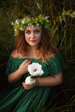 Young beautiful woman in green dress, to tell fortunes on a flower. The thoughtful dreamy gaze of the witch on you. Fabulous image. A luxurious wreath of wildflowers. Fashion toning. Creative color. Stock Photo