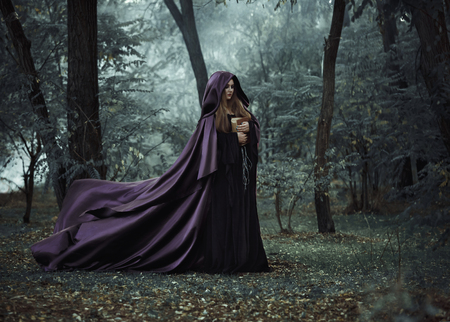 toning: On the eve of Halloween witch casts a spell, decided to collect a potion to brew, walking in the mysterious woods, keeping his book with conspiracies. Fabulous and mystical concept. Fashionable toning. Creative color. Stock Photo