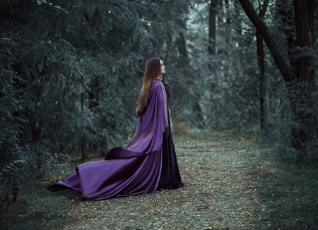toning: On the eve of Halloween witch casts a spell, decided to collect the potion to cook, walk in the mysterious forest. Fabulous and mystical concept. Fantastic shooting in the wild. Fashionable toning. Creative color. Stock Photo
