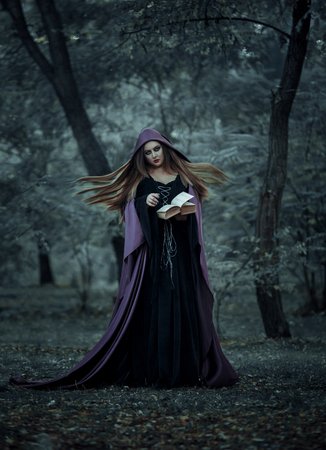 magic young: Beautiful young witch Halloween wearing vintage Gothic dress with hood keeps the magic of an ancient book of spells in a mysterious forest. Fabulous and mystical concept. Fantastic shooting in the wild. Fashionable toning. Creative color. Stock Photo
