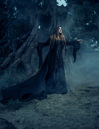 long night: Beautiful large Halloween witch, wearing a vintage Gothic dress with long sleeves and sweeping train. Arms outstretched, looking fly in dark night forest against the background, creepy tree. Fabulous and mystical concept. Fantastic shooting in the wild. F Stock Photo