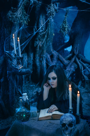 toning: On the eve of Halloween witch casts a spell, uttering a terrible spell over the ancient collection of arcane recipes. Fabulous, spooky voodoo shack. Candles, assorted bottles of potion. Fabulous and mystical concept. Fashionable toning. Creative color. Stock Photo