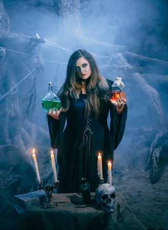 curse: On the eve of Halloween witch casts a spell, uttering a terrible curse on the bottles of potion and poison. Fabulous, spooky voodoo shack. Skeleton-Ghost.The mist and magic Shine. Fabulous and mystical concept. Fashionable toning. Creative color.