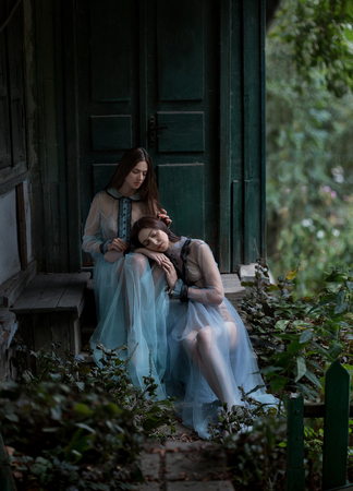 Two luxury brunette with long hair in vintage dresses, sitting on the threshold of the old house in front of the massive door. One lady put my head on my knees the other. Fantastic shooting in nature. Fashionable toning. Creative color.