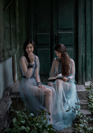 nude outdoors: Two luxury brunette with long hair in vintage dresses, they was sitting on the doorstep of the old house opposite the massive doors. One lady was reading a book and the other goddess smiled mysteriously.Fantastic shooting in nature. Fashionable toning. Cr Stock Photo