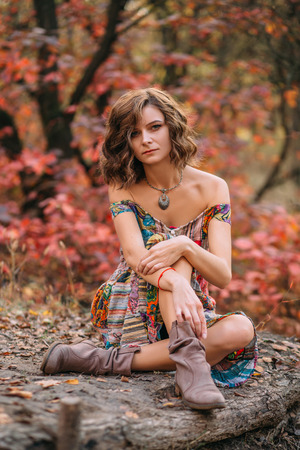 ritual: Luxury lady in a bright dress. She sits on the ground cross-legged showing boots. Fabulous Golden autumn trail. The picturesque nature. Boho style Fantastic shooting. Retro style. Fashionable toning. Creative color.