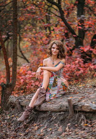Luxury lady in a bright dress. She sits on the ground cross-legged showing boots. Fabulous Golden autumn trail. The picturesque nature. Boho style Fantastic shooting. Retro style. Fashionable toning. Creative color.
