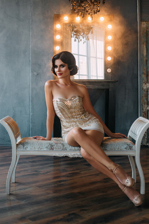 long sexy legs: Beautiful young woman with retro hairstyle on dark hair. Gracefully sitting on a bench crossing her long, sexy legs. Fantastic shooting in a beautiful Studio. Fashionable toning. Creative color. Stock Photo