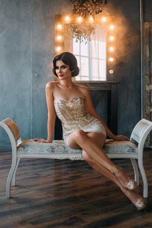 mujeres morenas: Joven y bella mujer con el peinado retro en el pelo oscuro. Elegantemente sentado en un banco de cruzar sus piernas largas y sexy. disparos en un hermoso estudio. tonificación de moda. color creativo.