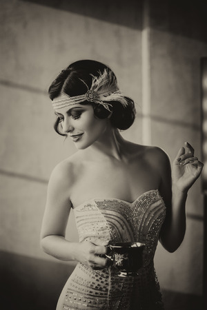 gracefully: Young beautiful woman is gracefully holding a Cup in one hand.Elegant hairstyle on dark hair. Exclusive dress, decoration on head in retro style.Fantastic shooting.Fashionable toning.Monochrome style.