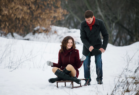 he she: Funny man and a beautiful girl, they walk together, she smiles playfully. He rolls her on a sled. A romantic feeling. Scenic winter walk in Park. Fantastic shooting. Fashionable toning. Creative color.